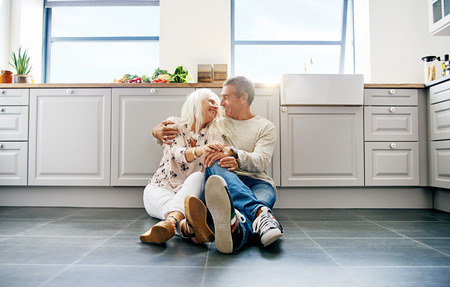 Cute senior couple looking at each other while seated comfortably on spacious dark tiled kitchen floor Stock Photo