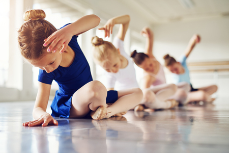 Little ballerinas doing exercises and bending sitting on floor in ballet class. 免版税图像