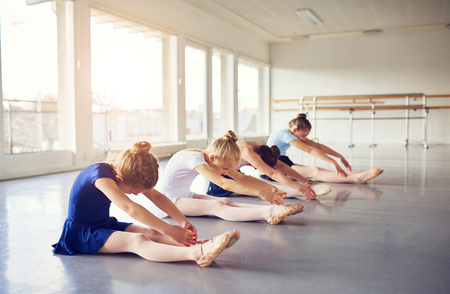 Little ballerina girls bending and stretching while sitting on floor in ballet class.