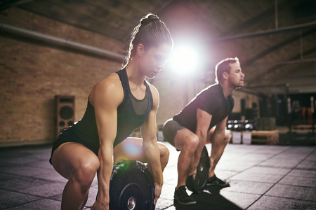 bodycare: Young man and woman in sportswear doing exercise with round weight disks from squat at gym. Stock Photo