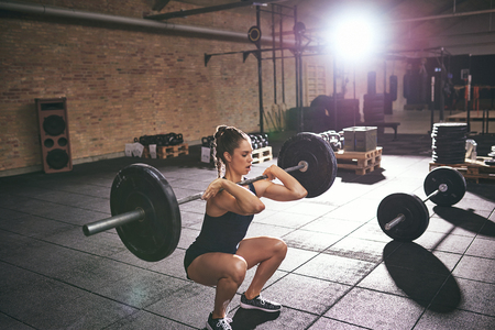 Young woman squatting while holding heavy barbell on shoulders in light gym. Stock Photo