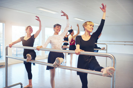 Group of adult women standing with hands up while doing gymnastics at handrail in ballet class. Imagens