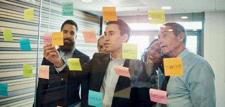 Group of businesspeople brainstorming, putting sticky note on glass Stock Photo