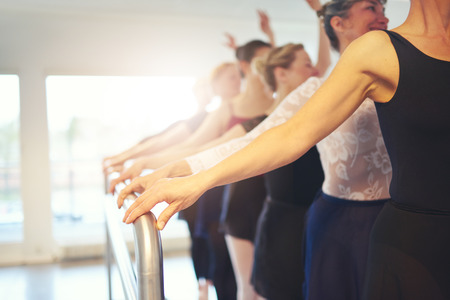 Hands of unrecognizable mature group of women holding handrail while performing a ballet in class together.