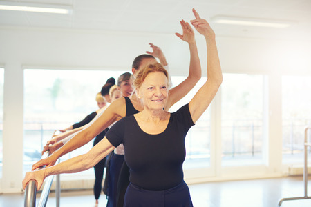 Ltere erwachsene Frau, die mit der Hand oben einen Tanz im Ballettunterricht steht. Standard-Bild - 83374597