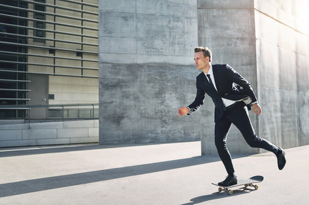 A successful businessman wearing suit riding a skateboard in the street. Banque d'images