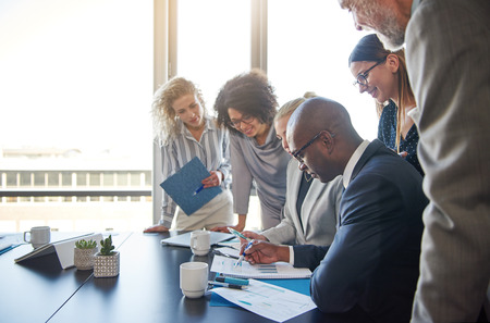 Group of diverse businesspeople smiling and working together around a boardroom table reviewing charts and paperwork Stock Photo