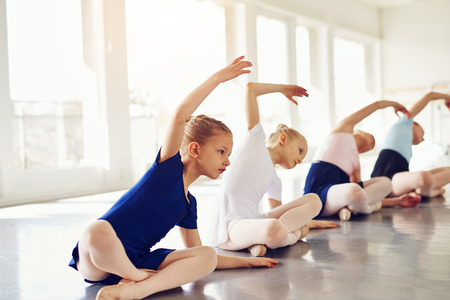 Adorable small ballerinas stretching and bending on floor of ballet class.