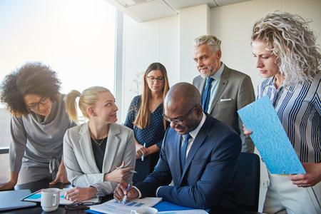 Diverse group of smiling businesspeople discussing paperwork together while having a meeting around a boardroom table in a modern office