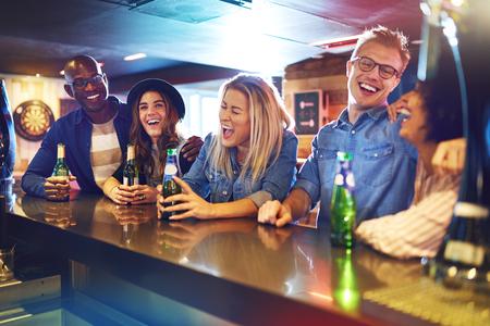 Plan horizontal à l'intérieur d'un groupe de personnes qui rit en train de rire au comptoir du bar. Banque d'images