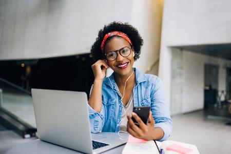 近代的なオフィスビルのロビーのテーブルで働いている間彼女の携帯電話で音楽を聴く若いアフリカの女性起業家を笑顔 写真素材