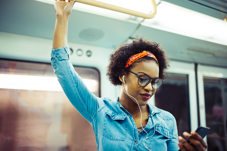 Smiling young African woman listening to music on her cellphone while standing on a subway train during her daily commute 스톡 콘텐츠