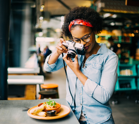 Young African woman standing alone at a counter in a bistro taking photos of her food with a vintage slr camera Foto de archivo
