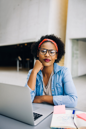 Smiling young African female entrepreneur wearing glasses sitting at a table in a modern office building lobby working on a laptop