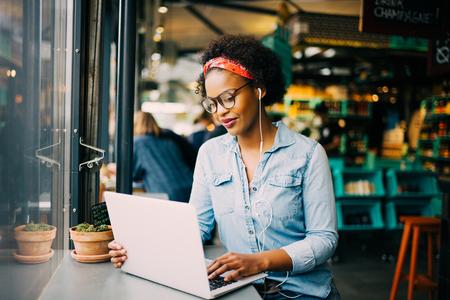 Mujer africana joven enfocada que se sienta solamente en un contador en un café que trabaja en una computadora portátil y que escucha la música en los auriculares Foto de archivo - 81065734