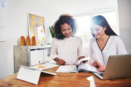 두 행복 젊은 여성 비즈니스 앉아 함께 사무실에서 페이징 보고서 또는 마케팅 전략을 연구 잡지를 통해 페이징 앉아