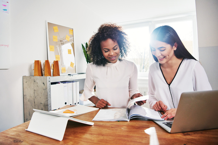 Two happy young women in business together sitting working at a desk in an office paging through a report or magazine researching marketing strategies