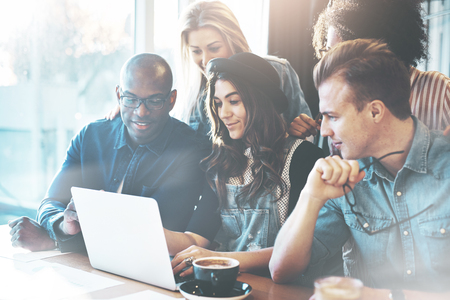 Multiracial business team made of determined young people looking at a laptop while working together in a modern office