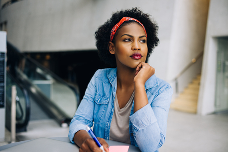 Young African female entrepreneur deep in thought while working at a table in a modern office building lobby