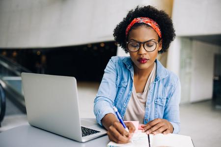 Entreprise féminine africaine focalisée assise à une table dans un hall d'immeuble de bureaux moderne travaillant sur un ordinateur portable et écrivant des notes dans son planificateur