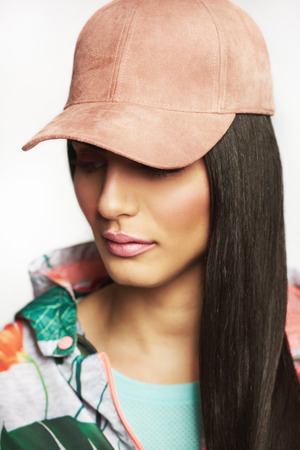 Studio portrait of pretty young girl wearing pink cap and casual bright clothes looking away.