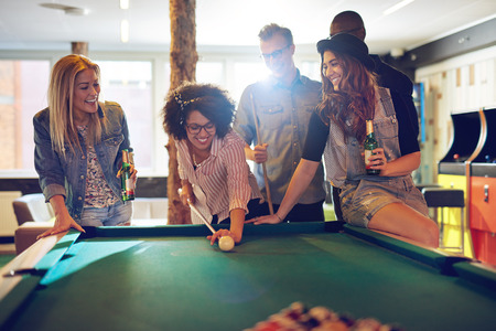 Smiling woman behind the cue ball while excited group of friends with beer surround the pool table watching