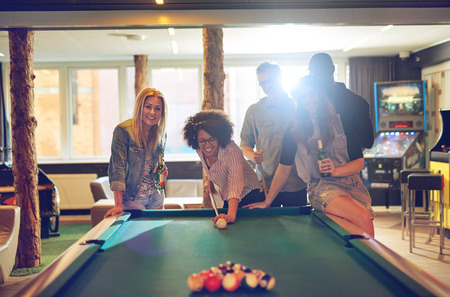 Group of five male and female friends in game room playing pool together while laughing and drinking beer