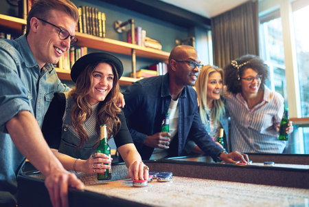 Group of mixed race friends having fun at bar playing a game and toasting with beer Stock Photo