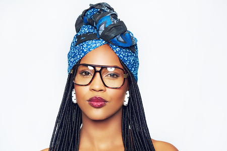 Portait of pretty young black woman in blue headscarf and trendy glasses, white background Stock Photo