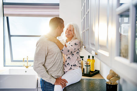 Smiling senior woman sharing a romantic moment with her husband while relaxing together in their kitchen at home