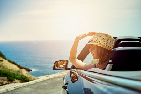 Back view of woman sitting in cabriolet putting hand on door looking away on background of sea.
