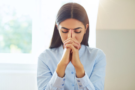 Front view on single young woman in blue long sleeve shirt praying or in deep thought with hands together at face