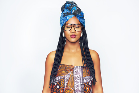 Beautiful African-American woman with glasses wearing traditional ethnic clothes and standing with eyes closed.