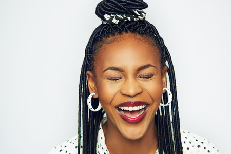 Cheerful African-American woman having fun and laughing with eyes closed.