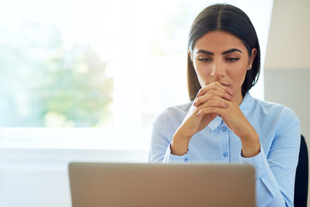 Serious young businesswoman with a worried expression sitting reading information on her laptop with clasped hands against a high window with copy space