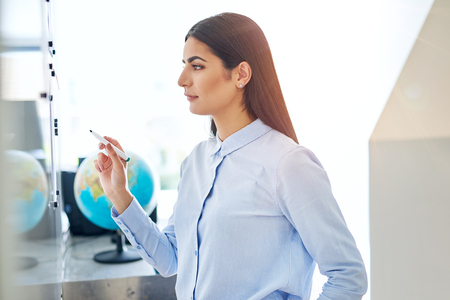 Serious young woman in blue at white board in classroom or small office with globe in background Imagens