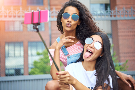 Two smiling young women sitting on a city bench making faces while taking self portraits together with a smartphone and selfie stick Stock Photo
