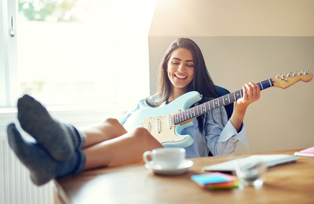 Beautiful girl singing while playing her electric guitar with feet on top of table Banco de Imagens