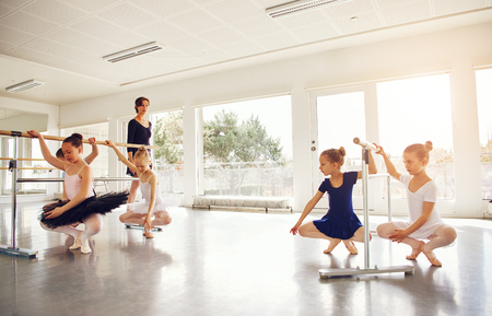 Group of cute children performing ballet while teacher watching them in ballet class. Stock Photo
