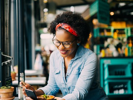 Smiling young African woman reading texts on a cellphone while sitting alone at a counter in a cafe enjoying a meal Stok Fotoğraf - 81436495