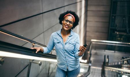 웃 고 현대적인 건물에 스 컬 레이 터를 혼자 승마하는 동안 그녀의 핸드폰에 음악을 듣고 젊은 아프리카 여자 스톡 콘텐츠