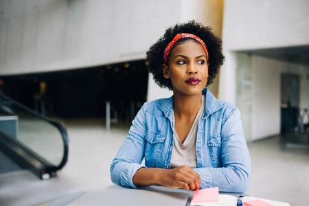 近代的なオフィスビル考え込んで探してロビーのテーブルで働く若いアフリカの女性起業家 写真素材
