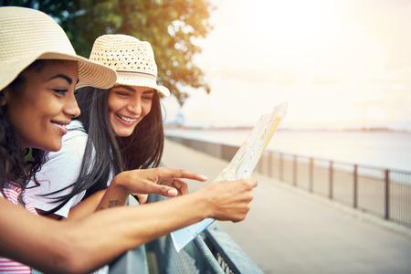 パスを実行することによって女性は手すりにもたれるし、フロッピーの夏用帽子を着用しながら地図を読む