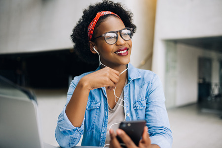 Attractive young African female entrepreneur listening to music on her cellphone while working at a table in the lobby of a modern office building Stock fotó