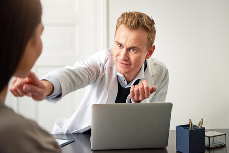 Spa and beauty professional man sitting at computer and touching chin of young female client.