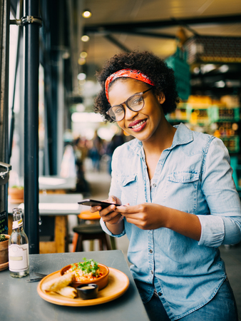 Stylish young African woman smiling while sitting at a counter in a bistro taking photographs of her food with her smartphone Stock Photo