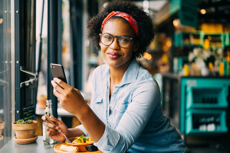 Smiling young African woman reading text messages on a cellphone while sitting alone at a counter in a cafe enjoying a meal