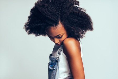 Shy young African girl with long curly hair and wearing dungarees standing sideways against a gray background