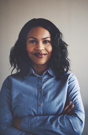 그녀의 팔을 사무실에서 혼자 서있는 웃는 젊은 아프리카 사업가의 초상화를 넘어 스톡 콘텐츠