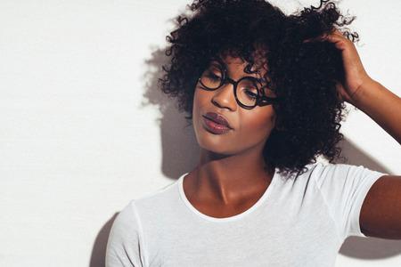 メガネと白い背景に対して彼女の毛で彼女の手に立って魅力的な若いアフリカ女性 写真素材 - 83523298